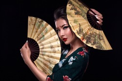 Fashion woman in image geisha. Beautiful attractive girl with hair bun, kimono, beauty stylised makeup. Two fans near the face