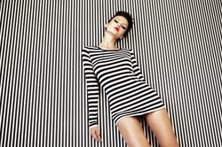 fashion woman in striped dress on striped background in studio