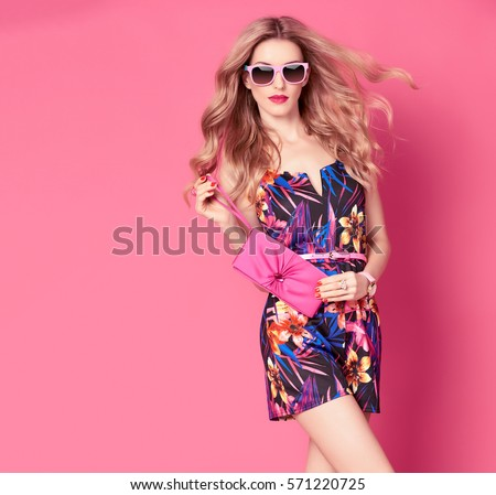Fashion woman in Trendy Spring Summer Dress. Stylish wavy hairstyle, fashion Sunglasses, Summer Floral Outfit. Glamour Blond lady in Sexy Jumpsuit, fashion pose. Playful Girl,Luxury summer Pink Clutch #571220725