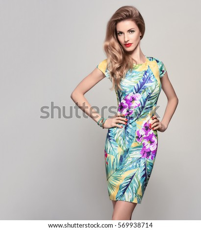 Fashion woman in Trendy Spring Summer Dress. Stylish wavy hairstyle, Makeup, Summer Floral Outfit. Glamour Blond lady in Sexy Bodycon. Playful Girl, Luxury Accessories