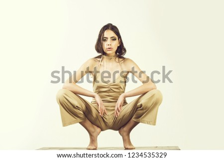 fashion woman in underwear overall has long hair and fashionable makeup, girl isolated on white background sitting barefoot #1234535329