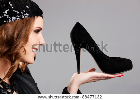 Fashion woman looking at high-heel shoes and smiling