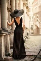 Fashion Woman Model in Hat Back Side View on Old City Street. Elegant Traveler Girl in Black Dress Looking at Antique Architecture. Stylish Lady in Black Gown and Hat