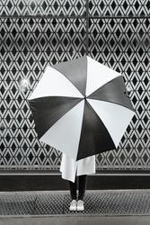 Fashion woman portrait holding umbrella against patterned wall background. White and black color theme conceptual photo. Geometric shapes, unique creative ways