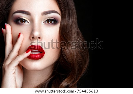 Fashion woman portrait on black background with red shiny lips.
