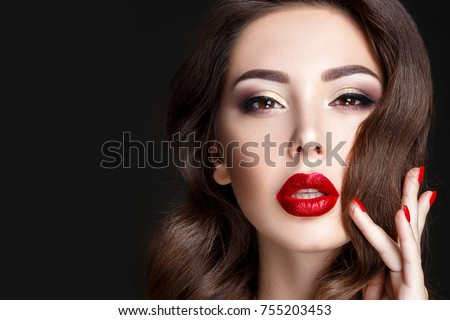 Fashion woman portrait on black background with red shiny lips and red nails.