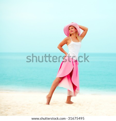 fashion woman posing near the ocean in pink clothes