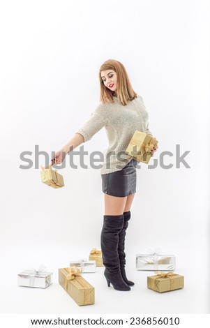 Fashion Woman posing with beautiful gifts in gold and silver packaging for Christmas holiday, isolated on white background. Glittered Ribbons and sweater for new years eve