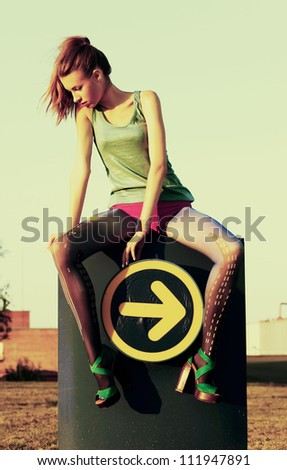 Fashion woman sitting on road sign indicating direction guide icon - arrow. Grunge, sepia style