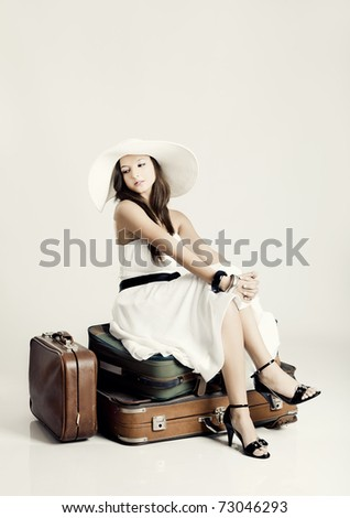 Fashion woman sitting over her luggage and waiting, isolated on a grey background