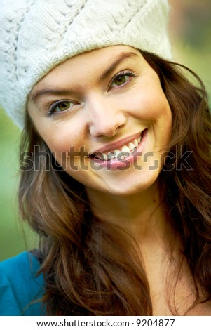 fashion woman smiling outdoors and wearing a hat