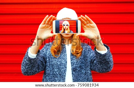 Fashion woman takes a picture self portrait on smartphone on red background