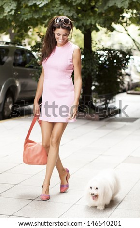Fashion Woman Walking In The Street With Her Dog