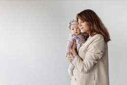 Fashion woman with cute newborn baby girl in studio, smiling, loving mother hold beautiful little daughter in arms, enjoy happy moments with child, maternity concept