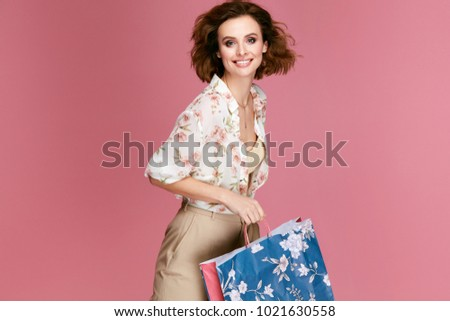 Fashion. Woman With Shopping Bags In Fashionable Clothes  On Pink Background. Happy Smiling Young Female Model In Stylish Clothing Holding Colorful Paper Bags. Women Style. High Quality Image.