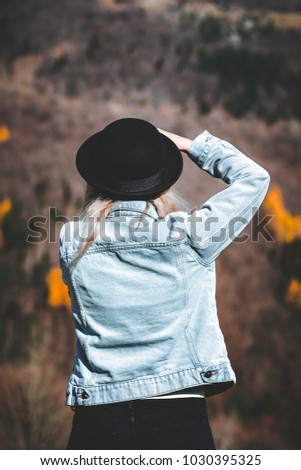 Fashion women photographer taking amazing landscape pictures. She's wearing a nice casual outfit with blue denim jacket, black jeans and a hat. #1030395325
