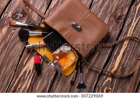 Fashion women\'s handbag. Open ladies handbag with scattered accessories.