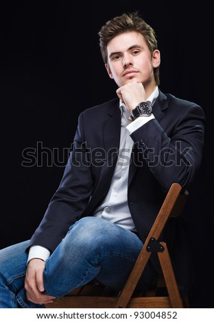Fashion young businessman black suit on dark  background