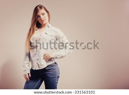 Fashion. Young long hair fashionable woman jeans pants shirt. Female model posing text area filtered photo