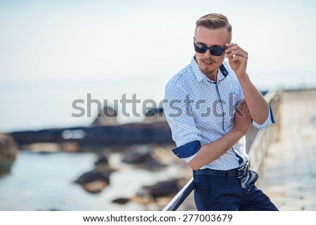 Fashion young man holding his fashionable sunglasses outdoor