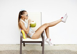 fashion young woman  drinking coconut water and sitting on chair . Outdoor lifestyle portrait
