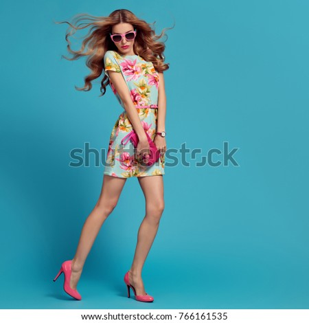 Fashion Young woman in Floral Dress. Glamour Sexy Blond Model. Trendy, Stylish wavy Hairstyle, Sunglasses, Heels. Playful Summer Girl on Blue
