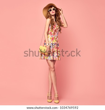 Fashion Young woman in Floral Dress. Pretty Girl in Hat, Sunglasses. Female model in Stylish Summer Outfit. Pink Vanilla Color. Beautiful Lady in Yellow Heels. Vintage #1034769592