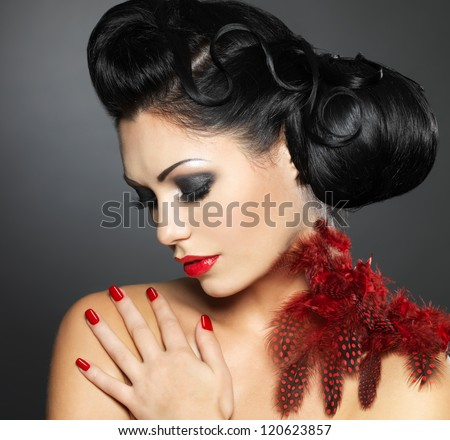 Fashion young woman with red nails, creative hairstyle and makeup - Model posing in studio