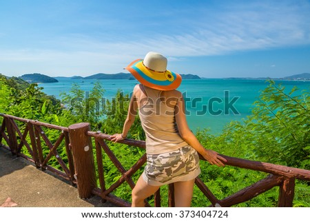 Fashionable and attractive woman tourist looks the spectacular view at Khao Khad View Point, Cape Panwa, Phuket, Thailand. #373404724