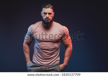 Fashionable and muscular with beard guy dressed in shirt and pants posing dark background. Foto d'archivio ©