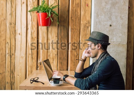 Fashionable and stylish young man talking on the phone, relaxing with coffee, music and internet browsing at the cafe bar. Selective focus. Profile shot. Toned image #293643365