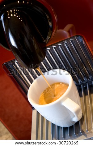 Fashionable automatic coffee machine pouring a fresh classic italian espresso in a small porcelain cup