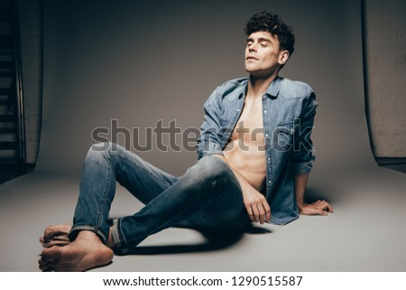 fashionable barefoot sexy man in jeans clothes relaxing on dark grey