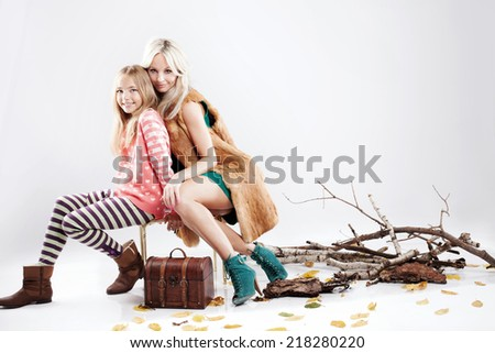 Fashionable beautiful blonde woman posing with her pretty daughter, looking at camera. Autumn photo