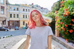 Fashionable beautiful girl teenager 16, 17 years old in wireless headphones with bright dyed colored hairstyle on the street of summer sunny city. Lifestyle, youth, fashion, beauty
