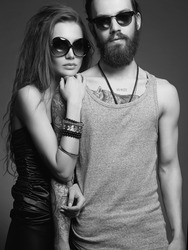 fashionable beautiful lovely couple in sunglasses. bearded Hipster boy and beauty girl with tattoo