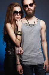 fashionable beautiful lovely couple in sunglasses. bearded Hipster boy and beauty girl with tattoo over blue background