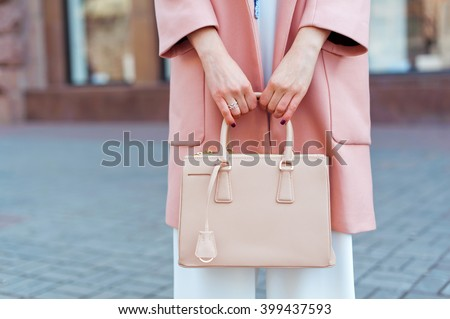 Fashionable beautiful woman with handbag in pink coat, white overalls and blue shoes on the city streets.