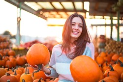 Fashionable beautiful young girl at the autumn pumpkin patch background. Having fun and posing. Toned in retro style