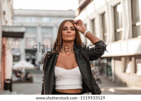 Fashionable beautiful young woman in stylish clothes with natural make-up with brown hair posing in the city. Attractive girl fashion model outdoors. Trendy autumn clothes. #1519933529