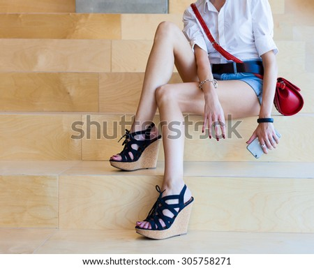 Fashionable beautiful young woman with long legs sitting on wooden stairs with a phone in her hand
