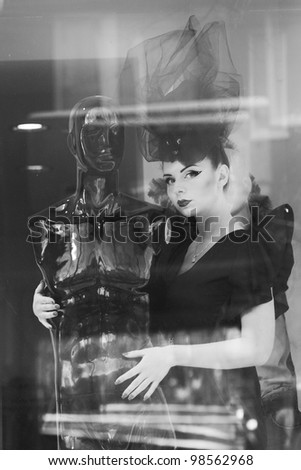 Fashionable beauty brunette woman behind a window