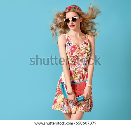 Fashionable Blond female model, Trendy Sunglasses. Stylish Glamour Summer Outfit. Young Beautiful European girl Posing in Studio. Gorgeous woman in Floral Dress, Wavy Hair