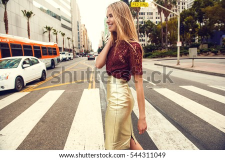 Fashionable blonde woman in red top and nice gold skirt, sunglasses walking in the street. Fashion spring summer photo Stock photo ©