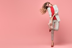 Fashionable blonde woman in Trendy elegant outfit, stylish hairstyle, makeup. Joyful funny lady in jacket dance on pink. Cheerful girl, stylish fashion accessories, beauty style, fun concept