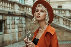 Fashionable blonde woman wearing  orange hat, trench coat, pearl necklace, ring, posing in street of European city. Copy, empty space for text