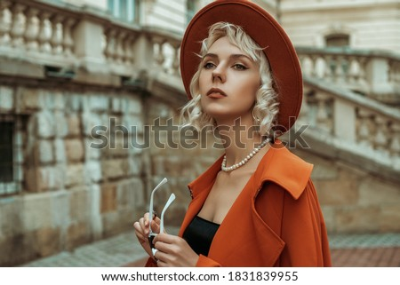 Fashionable blonde woman wearing  orange hat, trench coat, pearl necklace, ring, posing in street of European city. Copy, empty space for text Сток-фото ©