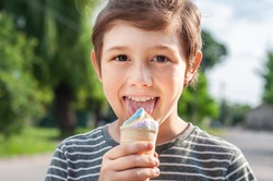 Fashionable boy eating multicolored ice cream in a waffle cone. Cool in the summer heat. Sweet snack. Hot Summer. Emotional child licks ice cream
