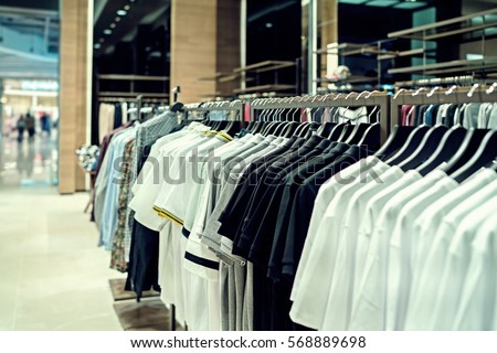 fashionable brand new for sale - interior of cloth store. shirts at shelf in shop shopping mall. #568889698