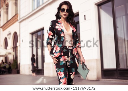 Fashionable brunette woman dressed in nice clothes, sunglasses walking in the street. Fashion spring summer photo #1117693172
